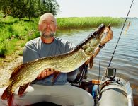 happy fisherman catching giant pike