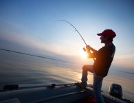 Young man fishing from the boat at sunset